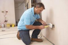Elektriker, der Wand-Einfaßung installiert Stockfotografie