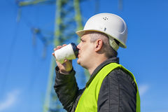 Elektriker-Engineer-Getränk nahe Hochspannungsturm Stockfoto