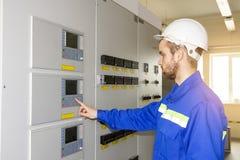 Elektriker Engineer på kontrollbräde Arbetaren kontrollerar industriella processar royaltyfria bilder
