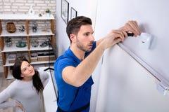 Elektriker-Installing Security System-Bewegungs-Detektor auf Wand stockbild