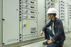 Elektriker kontrollerar elektriska kontrollbord i industrianl?ggningar royaltyfri bild