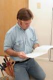 Elektriker liest das Handbuch Stockfotos