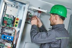Elektriker machen Wartung im Maschinenraum des Aufzugs lizenzfreie stockbilder