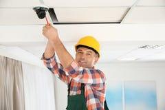 Elektriker med skruvmejsel som reparerar CCTV-kameran arkivfoto