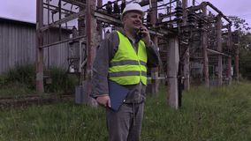 Elektriker med smartphonen och dokumentation som går i avdelningskontor stock video