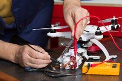 Elektriker på arbete med en quadcopter Fotografering för Bildbyråer