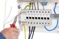 Elektriker repariert einen Draht auf einem Stromkreis stockfotografie