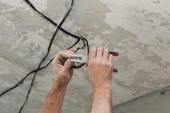 Elektriker säubert die Kontakte mit Zangen Installierung der Deckenleuchte stockbilder
