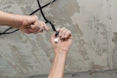Elektriker säubert die Kontakte mit Zangen Installierung der Deckenleuchte lizenzfreie stockbilder