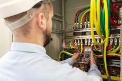 Elektriker som arbetar med multimeteren i elektriskt kabinett arkivfoton
