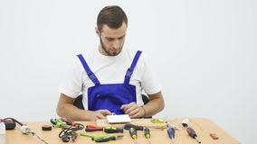 Elektriker som arbetar på hans skrivbord lager videofilmer