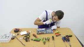 Elektriker som arbetar på hans skrivbord arkivfilmer