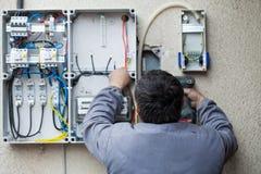 Elektriker som fixar en säkring royaltyfri bild