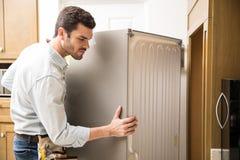 Elektriker som flyttar en kyl i ett kök arkivbilder