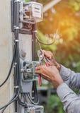 Elektriker som installerar den elektriska metern för att mäta makt in i den elektriska linjen fördelningsfuseboard Royaltyfri Fotografi