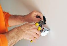 Elektriker som installerar elektriska strömbrytare i det nya huset Arkivfoto