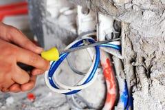 Elektriker som installerar en strömbrytarehålighet royaltyfria bilder