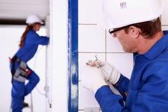 Elektriker som installerar håligheten royaltyfri foto
