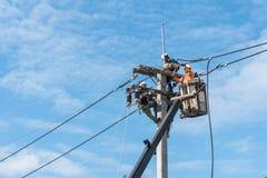 Elektriker som installerar nya kraftledningar Arkivfoto