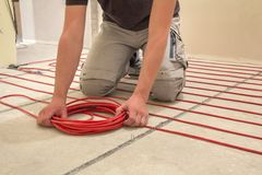 Elektriker som installerar värma röd tråd för elektrisk kabel på cementgolv i litet nytt oavslutat rum med packade väggar arkivbilder