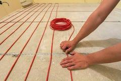 Elektriker som installerar värma röd tråd för elektrisk kabel på cementgolv i oavslutat rum Renovering och konstruktion, royaltyfri foto