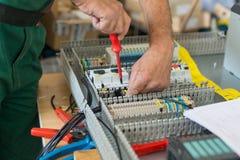 Elektriker som monterar det industriella elektriska kabinettet Royaltyfri Bild