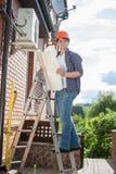 Elektriker som ser ritningar och plan av det betingande systemet för luft på huset Royaltyfri Foto