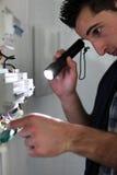 Elektriker som skiner en fackla arkivbild