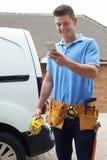 Elektriker With Van Texting On Mobile Phone außerhalb des Hauses Stockfoto