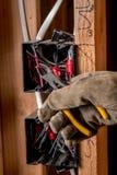 Elektrikerarbeiten über etwas Drähte in einem elektrischen Kasten lizenzfreies stockfoto