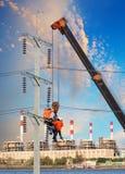 Elektrikerarbeitskraft, die an elektrischem Hochspannungspfosten mit Cr arbeitet Stockfotos