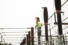Elektrikerbyggmästaretekniker Elektricitetstransformator på en kraftverk Arkivfoto