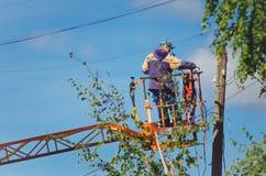 Elektrikeren ändrar trådarna på polen arkivbilder