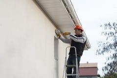 Elektrikeren installerar en lampa royaltyfri bild