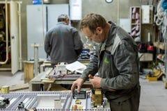 Elektrikeren monterar och justerar den elektriska kontrollbordet Arbeten på montering av den elektriska strömkretsen av a Royaltyfri Foto
