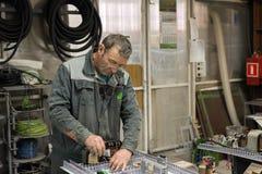 Elektrikeren monterar och justerar den elektriska kontrollbordet Arbeten på montering av den elektriska strömkretsen av a Royaltyfri Bild