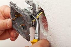 Elektrikeren räcker installation av trådar in i elektriskt uttag Arkivfoto