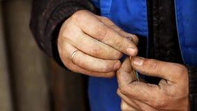 Elektrikeren samlar LAN-kabel, tillsammans som han har smutsig händer och kläder arkivfilmer