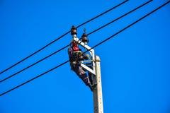 Elektrikeren utför underhåll på överföringstornen med bruk av det jordluckraremanhål och bältet Arkivfoto