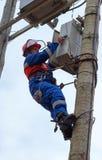 Elektrikeren utför underhåll på överföringstornrecloen Arkivfoto