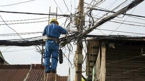 Elektrikerfestlegung, unordentliche elektrische Leitungen in Hanoi-Elendsvierteln reparierend, Vietnam Stockfoto