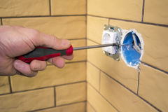 Elektrikerhand med skruvmejseln som installerar håligheten Royaltyfria Bilder