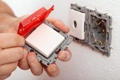 Elektrikerhand som ändrar eller installerar en elektrisk strömbrytare Royaltyfri Foto