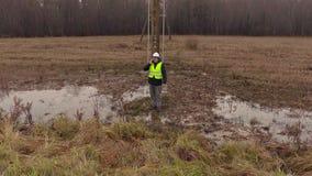 Elektrikeringenieur, der am Telefon an den Hochspannungspfosten spricht stock footage
