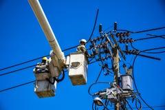 Elektrikerlinjearbetare som reparerar arbete på elektrisk stolpemaktpol Royaltyfri Bild