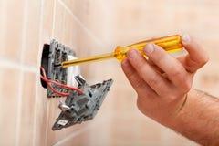Elektrikerprovning för elektricitet i elektriskt väggfast tillbehör arkivfoto