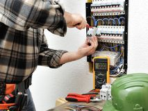 Elektrikertechniker bei der Arbeit über eine elektrische Wohnplatte Stockfoto