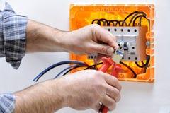 Elektrikertechniker bei der Arbeit über eine elektrische Wohnplatte lizenzfreie stockfotografie