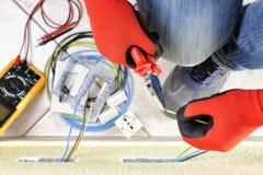 Elektrikertechniker bei der Arbeit mit Schutzausrüstung auf einem elektrischen Wohnsystem stockfotos