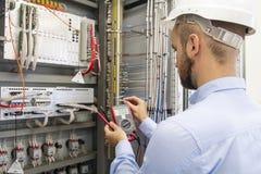 Elektrikertekniker i säkringsask Underhållstekniker i kontrollbord Arbetaren testar automationutrustning royaltyfri foto